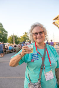 happy woman sips beer at Escapade street festival