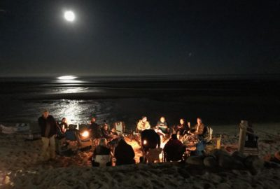 Group of Escapees around a campfire on the beach