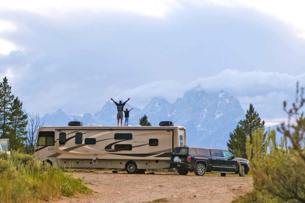 Father and son stand on RV facing mountains