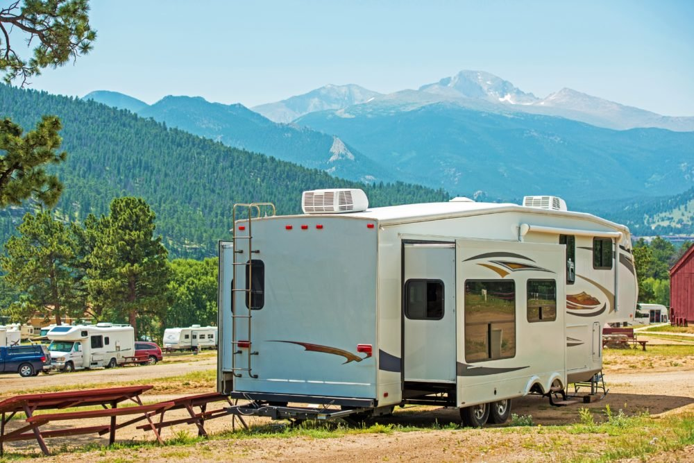 5th wheel RV in campground with mountain background