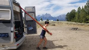Woman uses elastic bands to workout by RV van