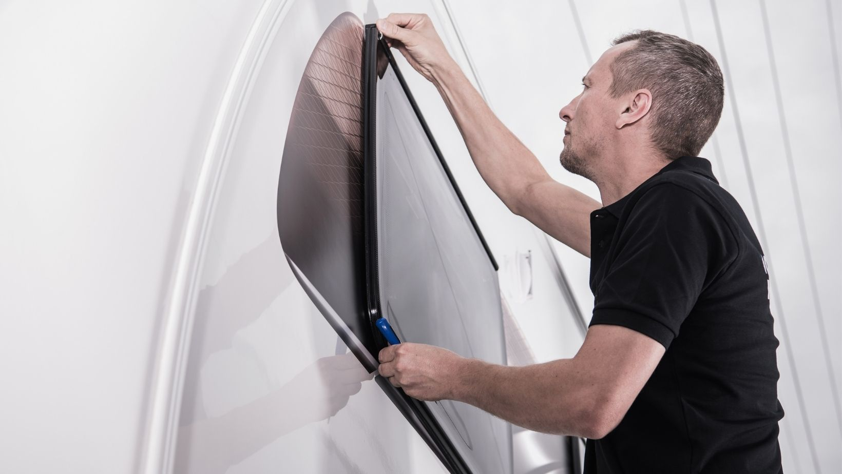 Man repairing seal on RV window