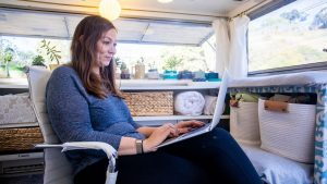 Woman works on computer in her RV