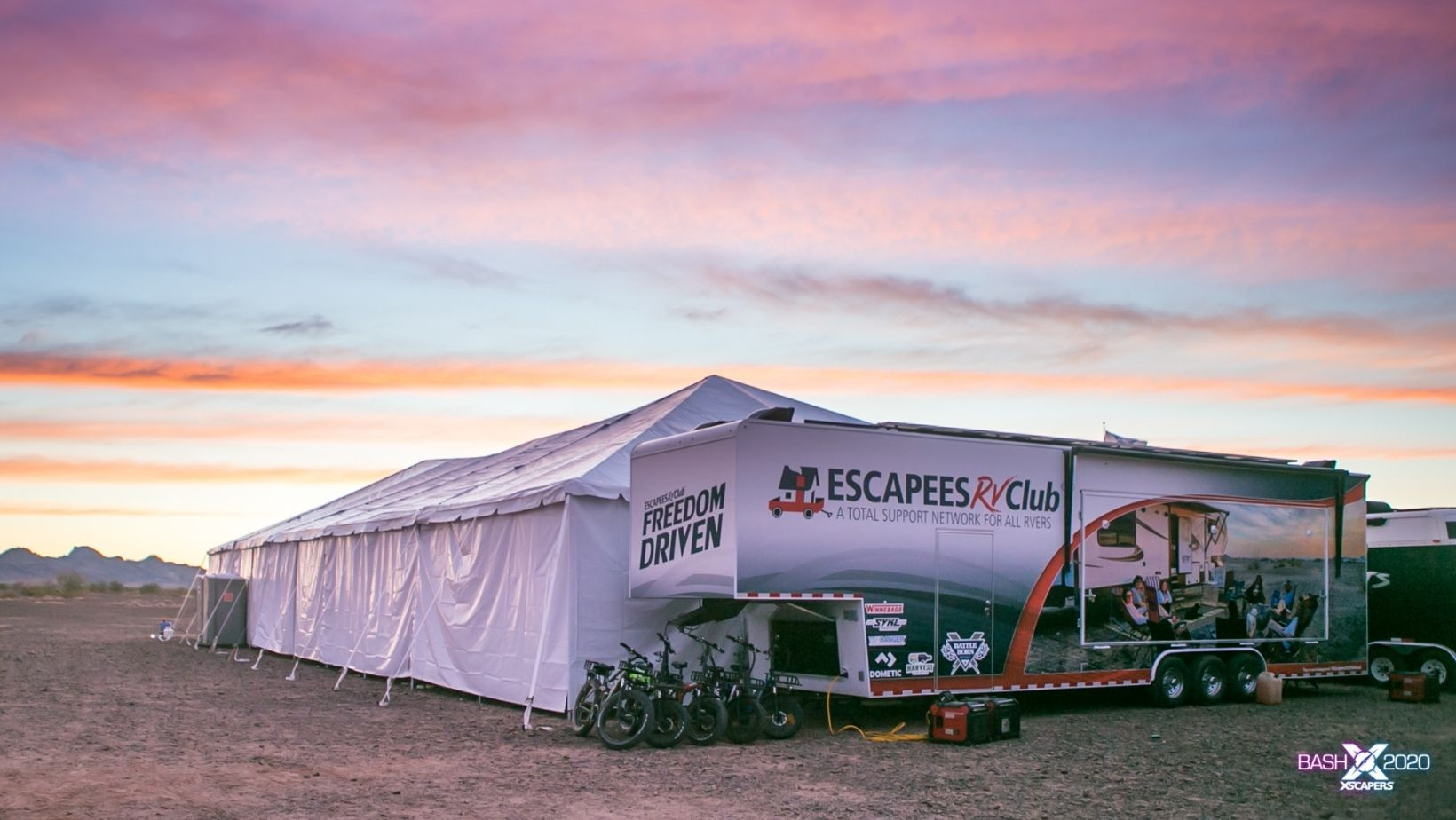 View of the entire Escapees event trailer with tent deployed and e-bikes parked nearby.
